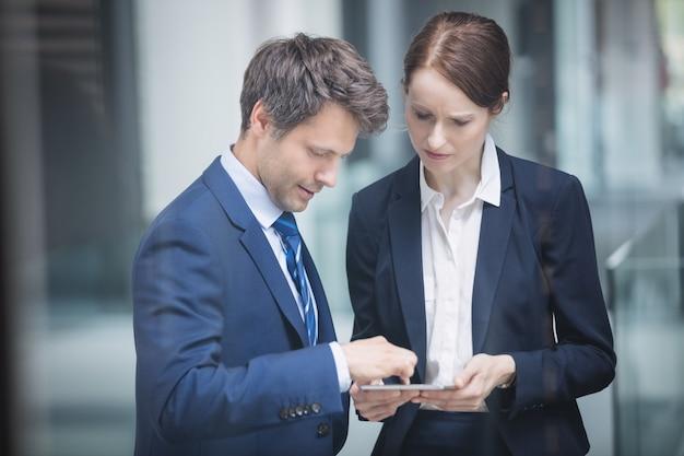 Uomo d'affari e collega che discutono sopra la compressa digitale