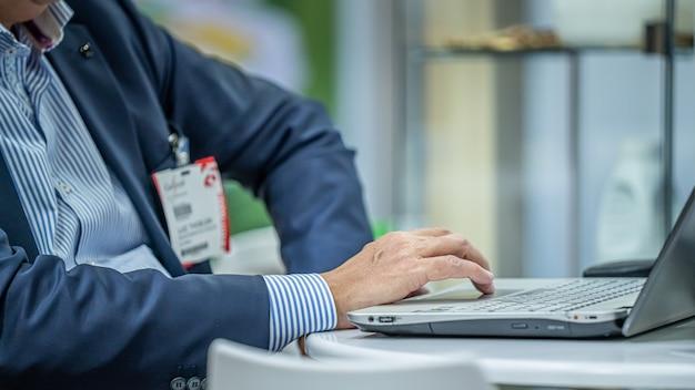 Uomo d'affari e computer portatile in fiera