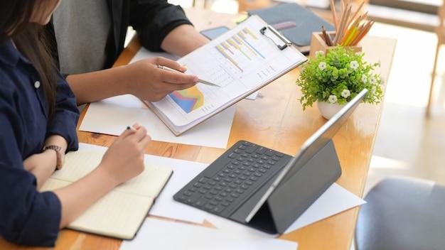 Uomo d'affari e donna di affari che si siedono alla tavola che lavora con i dati