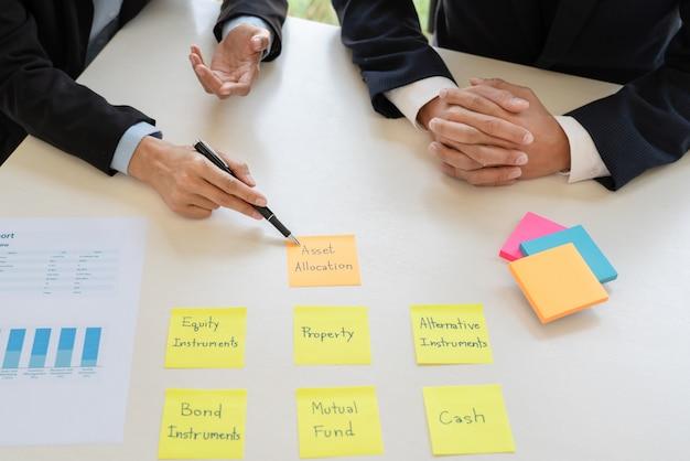 Uomo d'affari e gruppo che analizzano rendiconto finanziario