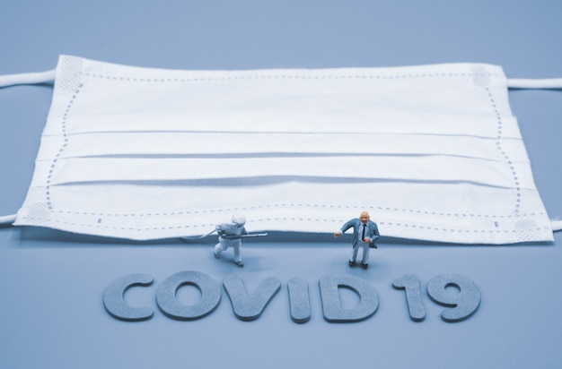 Uomo d'affari e medico in miniatura che indossano tuta protettiva personale con maschera, preoccupati per le questioni economiche e finanziarie durante la crisi mondiale covid-19. coronavirus, concetto commerciale e medico