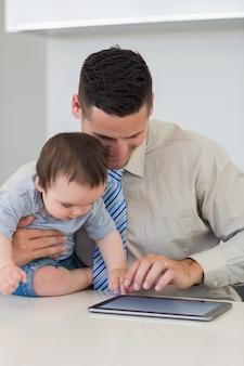 Uomo d'affari e neonato che per mezzo della compressa digitale
