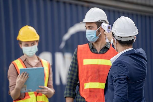 Uomo d'affari e operai che indossano maschere mediche