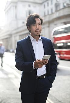 Uomo d'affari elegante che cammina nella via, indossando un vestito blu