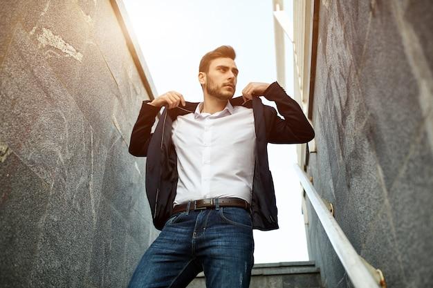 Uomo d'affari elegante ed alla moda in rivestimento che sta sull'edificio classico di architettura delle scale.