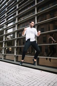 Uomo d'affari emozionante che salta in aria con gioia guardando cellulare