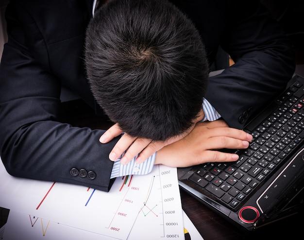Uomo d'affari esaurito e stanco che dorme nell'ufficio
