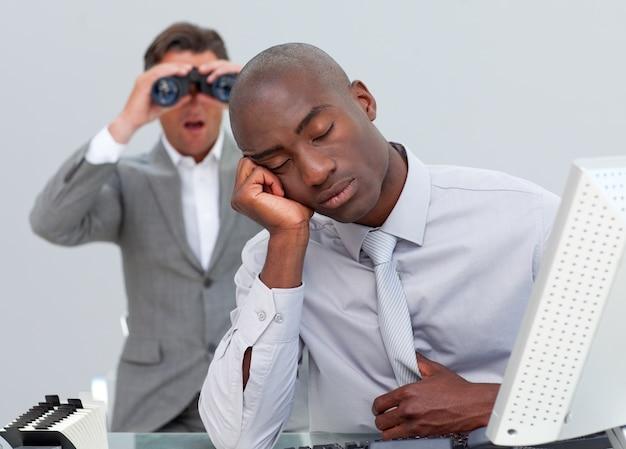 Uomo d'affari etnico infastidito da un uomo che guarda attraverso il binocolo