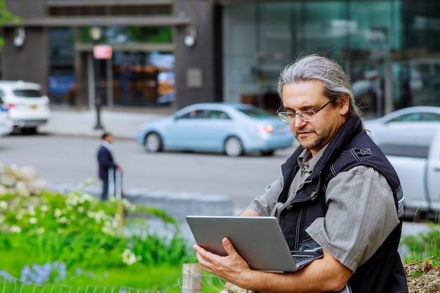 Uomo d'affari europeo in viaggio, lavorando a new york con i capelli grigi, lavorando su un computer portatile