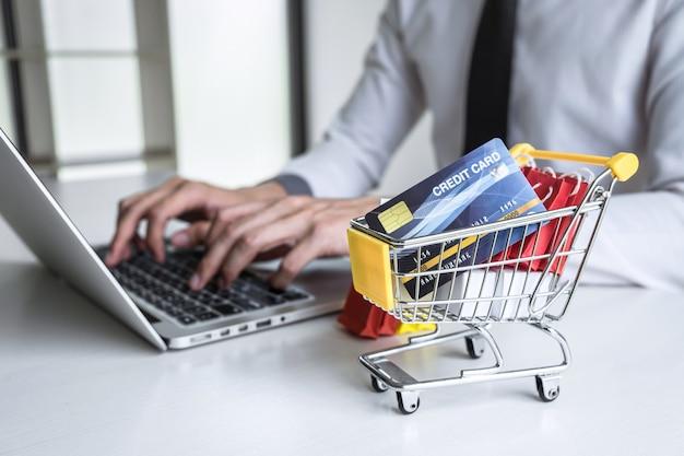 Uomo d'affari facendo uso del computer portatile e tenendo la carta di credito per il pagamento dell'acquisto online dell'esposizione della pagina del dettaglio