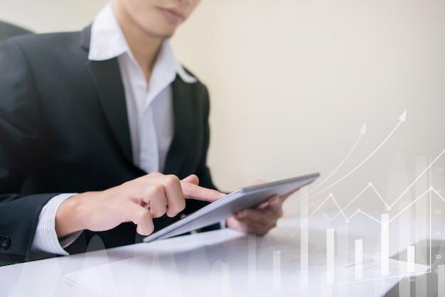 Uomo d'affari facendo uso del grafico del grafico di crescita economica di dati del controllo della compressa.