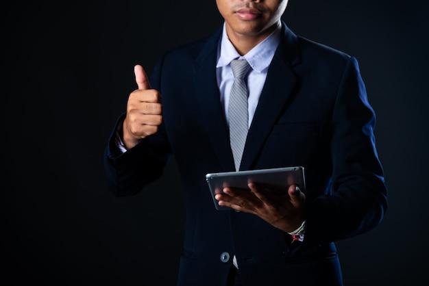 Uomo d'affari facendo uso della compressa che analizza i dati di vendite e grafico del grafico di crescita economica, tecnologia