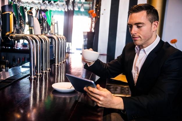 Uomo d'affari facendo uso della compressa che mangia un caffè al contatore in una barra