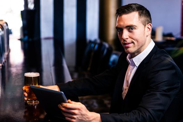 Uomo d'affari facendo uso della compressa che mangia una birra in una barra