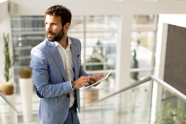 Uomo d'affari facendo uso della compressa dello schermo attivabile al tatto in ufficio moderno