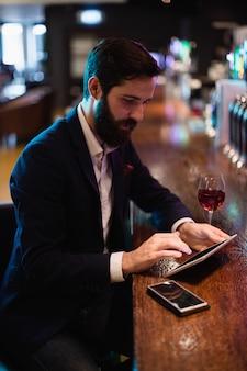 Uomo d'affari facendo uso della compressa digitale con il vetro di vino e telefono cellulare sul contatore