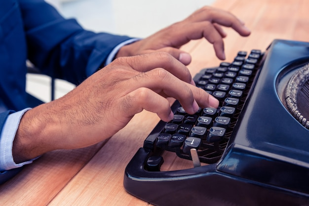 Uomo d'affari facendo uso della macchina da scrivere allo scrittorio di legno in ufficio