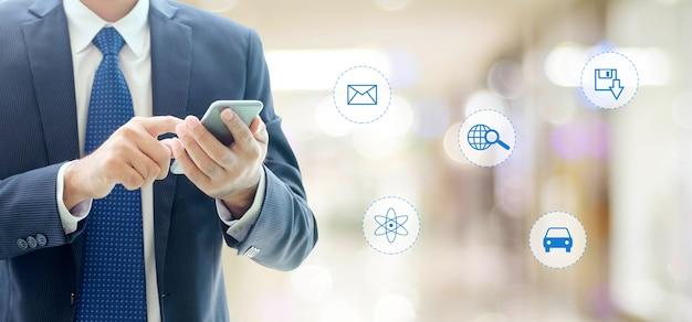 Uomo d'affari facendo uso dello smart phone con internet dell'icona di cose sul concetto vago del fondo, di affari e di tecnologia