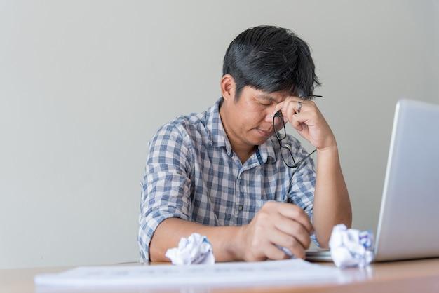 Uomo d'affari faticoso allo scrittorio con il computer portatile che cerca uscita dalla situazione difficile. l'uomo frustrato stressato premuroso lavora troppo a lungo sul computer, sceglie la soluzione, pensa a un problema difficile