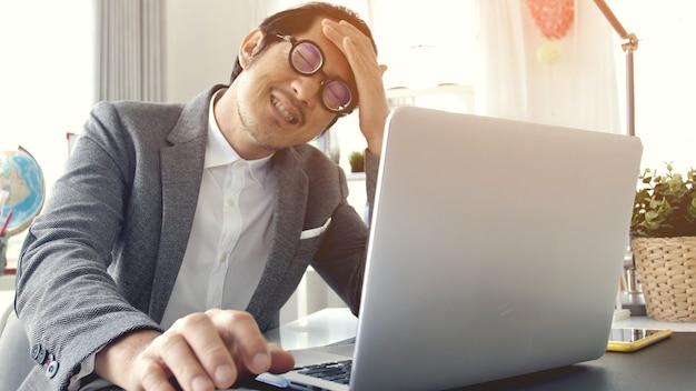 Uomo d'affari faticoso che ha mal di testa nell'ufficio,