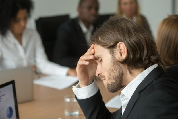 Uomo d'affari faticoso frustrato che ha forte emicrania alla riunione della squadra varia