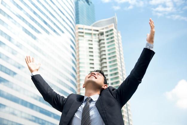 Uomo d'affari felice che alza le sue braccia nell'aria che si autorizza