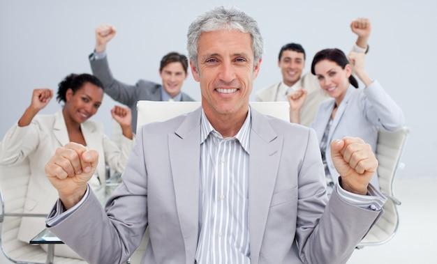 Uomo d'affari felice che celebra un successo con la sua squadra