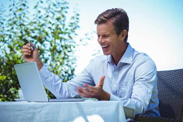 Uomo d'affari felice che fa spesa online con il computer portatile e la carta di credito