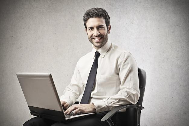 Uomo d'affari felice che lavora ad un computer portatile