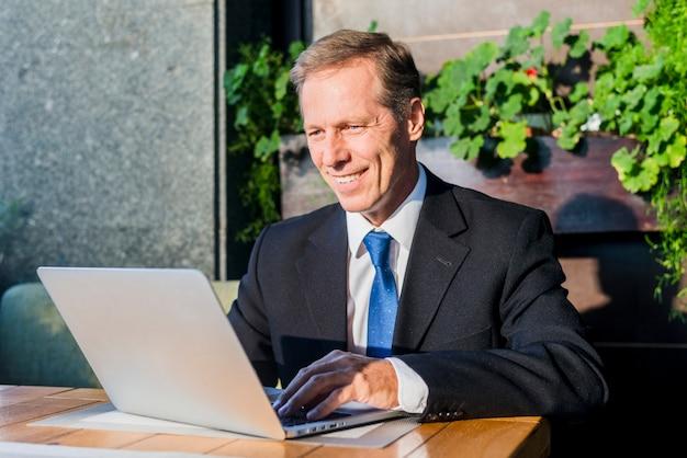 Uomo d'affari felice che lavora al computer portatile nel ristorante