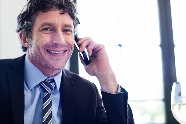 Uomo d'affari felice che parla sul telefono cellulare