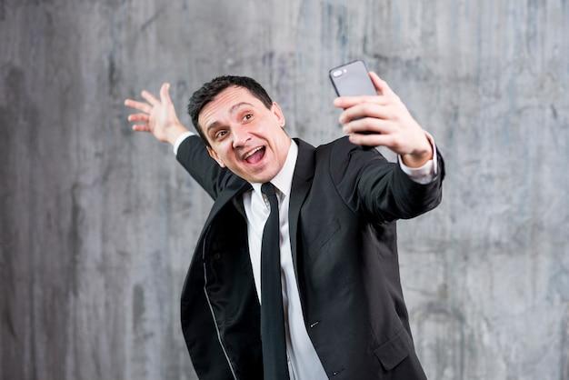 Uomo d'affari felice che solleva mano e prendendo selfie