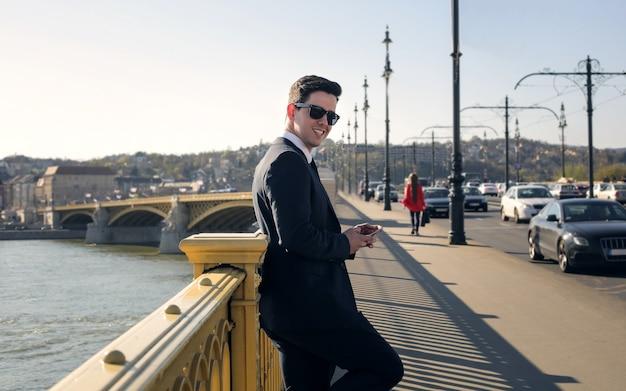 Uomo d'affari felice che sorride su un ponte in città