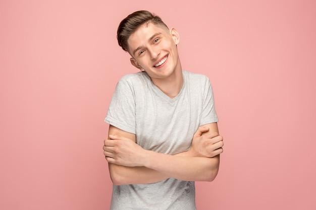 Uomo d'affari felice che sta e che sorride contro la parete rosa.