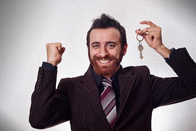 Uomo d'affari felice che tiene una chiave della casa