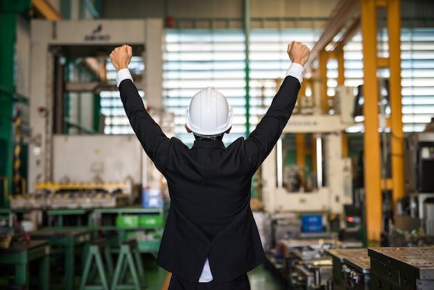 Uomo d'affari felice con il casco in fabbrica