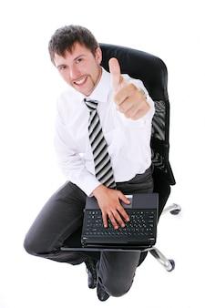 Uomo d'affari felice con il computer portatile che mostra segno giusto