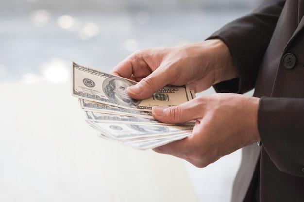 Uomo d'affari felice e riuscito che giudica le fatture di soldi del dollaro americano a disposizione.