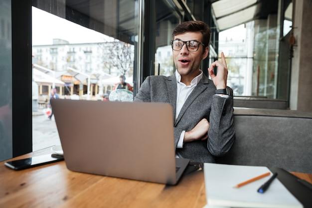Uomo d'affari felice in occhiali che si siedono dalla tavola in caffè con il computer portatile e che hanno idea