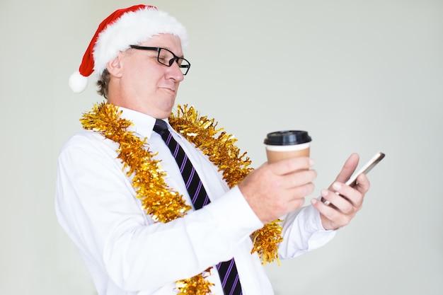 Uomo d'affari felice nel messaggio mandante un sms del cappello di santa