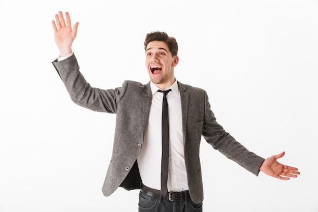 Uomo d'affari felice sorpreso in giacca agitando il palmo della mano e guardando lontano sul muro bianco