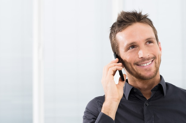 Uomo d'affari felice sul telefono cellulare