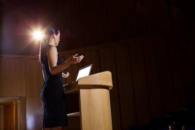Uomo d'affari femminile che dà un discorso