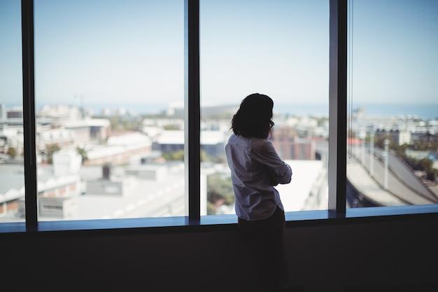 Uomo d'affari femminile che guarda attraverso la finestra