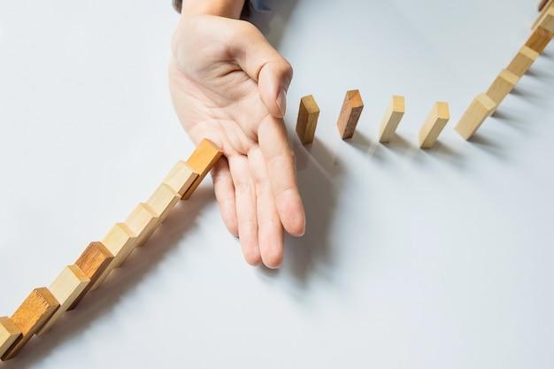 Uomo d'affari fermare domino continuo rovesciato o rischiare con copyspace