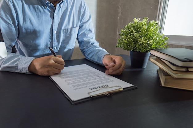 Uomo d'affari firma contratto sulla scrivania nera in ufficio.