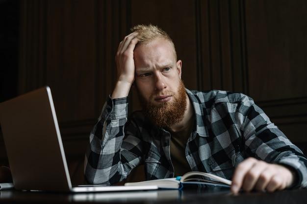 Uomo d'affari frustrato che si siede nell'ufficio