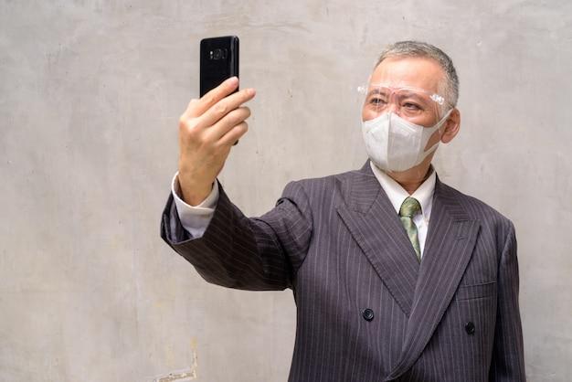 Uomo d'affari giapponese maturo con la maschera e la visiera che prendono selfie