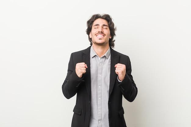 Uomo d'affari giovane alzando il pugno, sentirsi felici e di successo