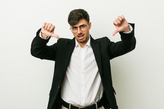 Uomo d'affari giovane che mostra il pollice verso il basso e che esprime antipatia.